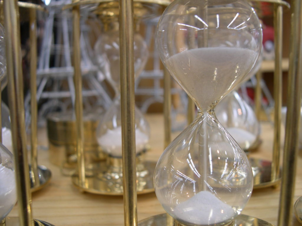 An hourglass counts down beside other identical hourglasses.