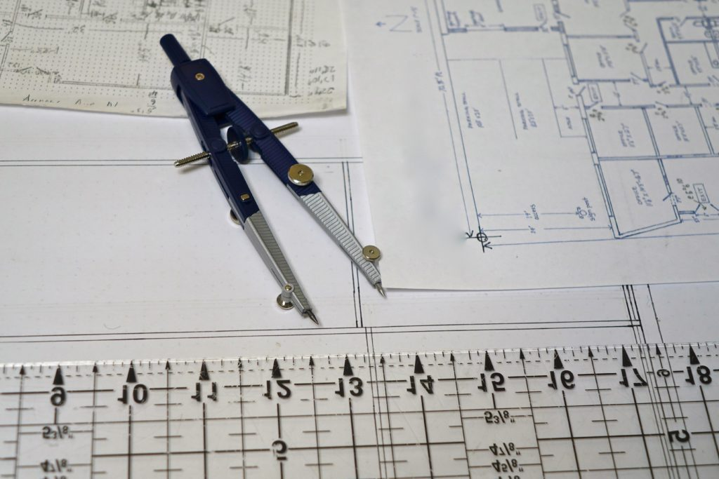 A compass and ruler on building plans.