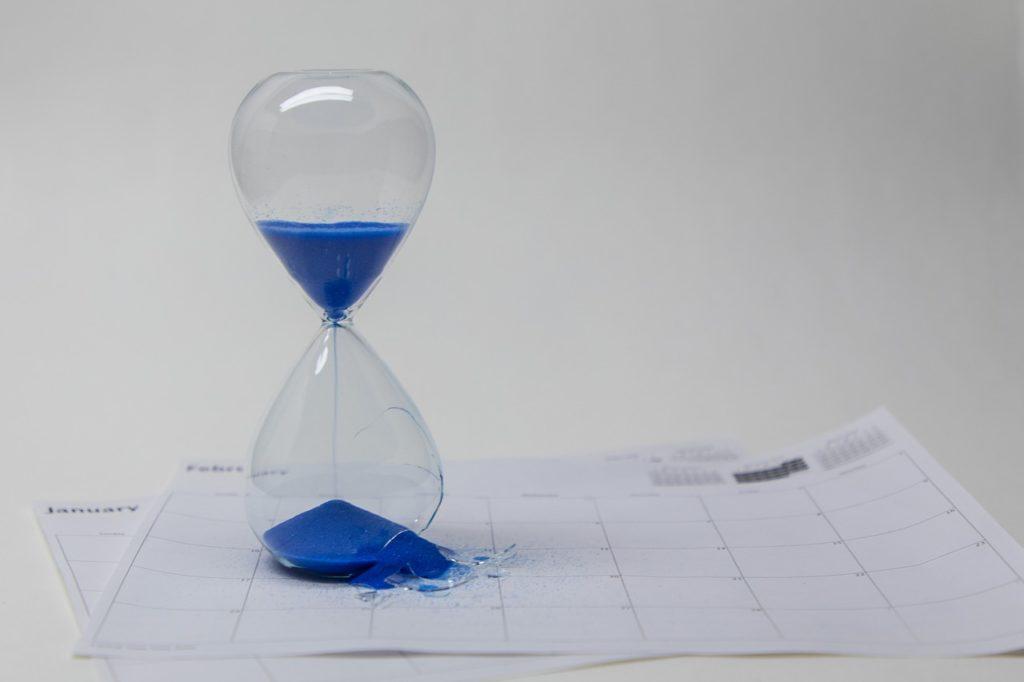 A broken hourglass on top of a calendar.