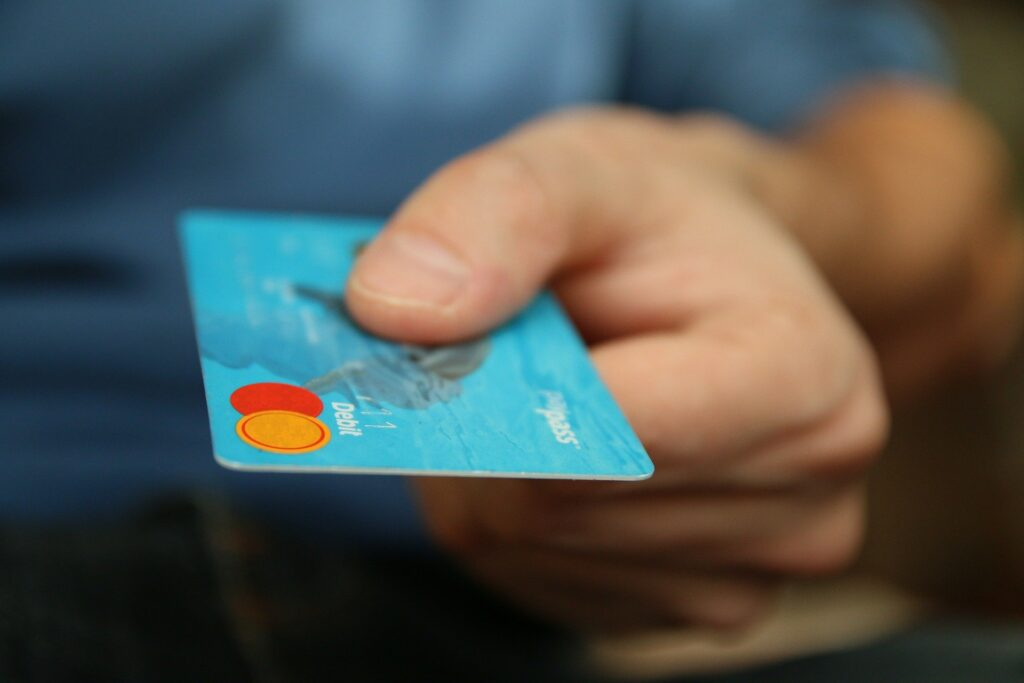 A hand holding out a credit card.