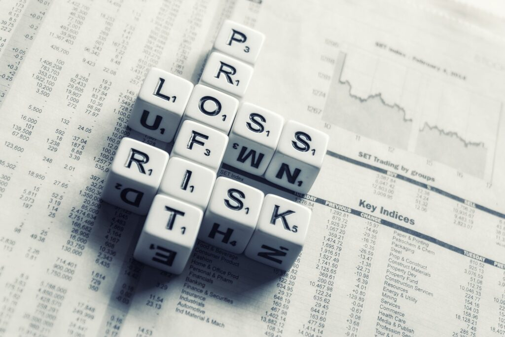 Dice spelling out profit, loss, and risk on a newspaper displaying stock market information.