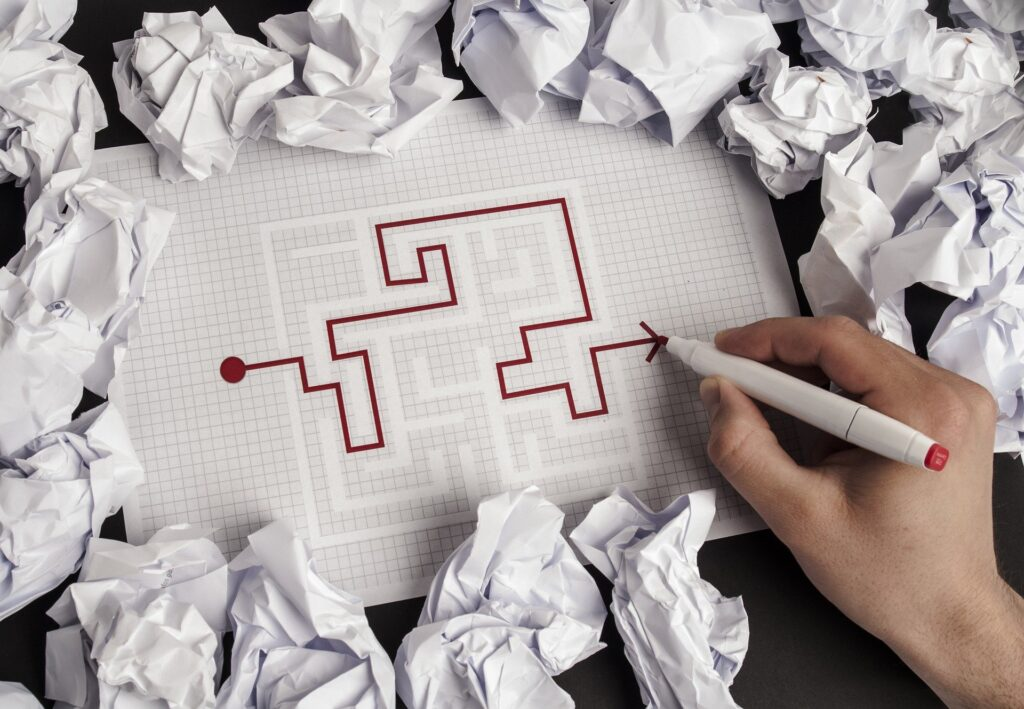 A solved maze surrounded by crumpled pieces of paper.