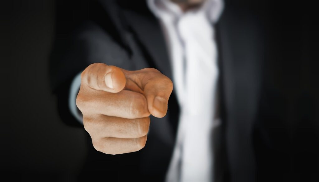 A man in a suit pointing.