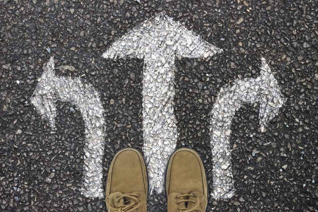 Three arrows on pavement pointing forward and to each side.