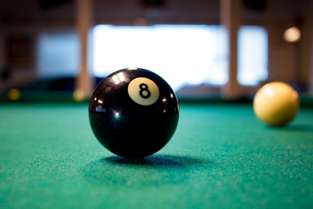 An eight ball on a pool table.