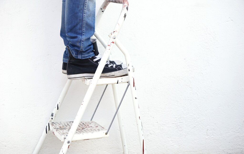 An individual standing on the top rung of a ladder.
