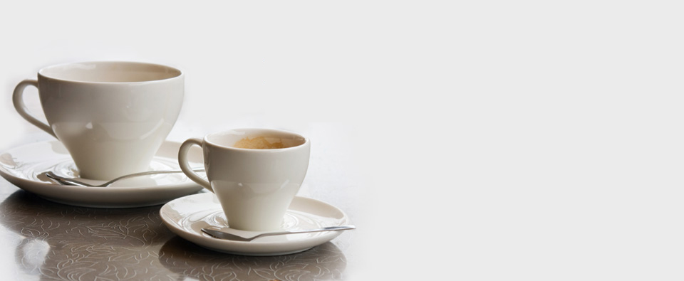 A coffee cup beside a smaller espresso cup, each with a saucer and spoon.